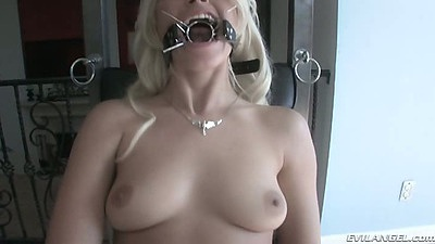 Lesbian wearing a mouth spreader in bdsm femdom fetish scene