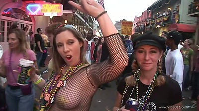 Dancing fishnet girl sin public during mardi gra outdoors on the street